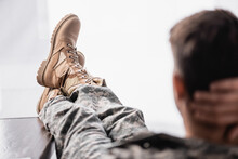 Military Boots On Soldier Resting On Blurred Foreground