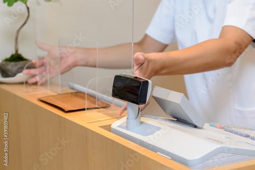 白衣を着た男性が受付に飛沫防止用のアクリル板を設置するシーン 感染症対策 新しい生活様式 Canvas-taulu