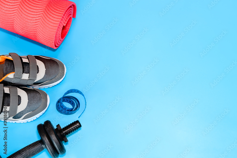 Fototapeta Sports accessories with copy space. Fitness concept set. Sneakers, sports mat, tapeline and dumbbells on blue background. - obraz na płótnie