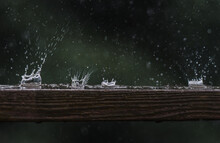 Close Up Of Raindrops Hitting A Wooden Railing With A Splash.
