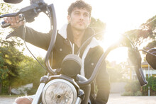 Man In Leather Jacket Sitting On A Motorcycle With The Sun's Rays Shining