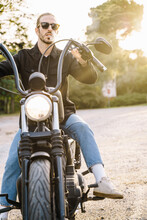 Vertical Photo Of A Young Man With Sunglasses Smoking While Sitting In Motorcycle