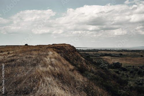 Landscape field, hillside and cloudy sky. Canvas Print