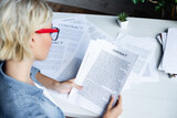 young blonde woman in eyeglasses working with documents