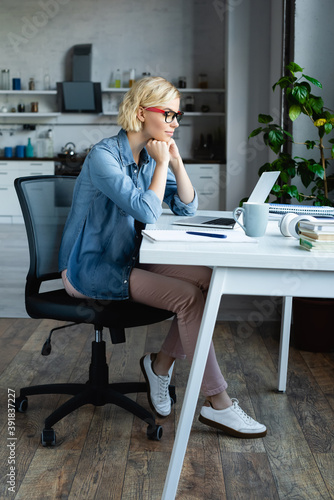 Obraz full length of young blonde woman in eyeglasses working from home - fototapety do salonu