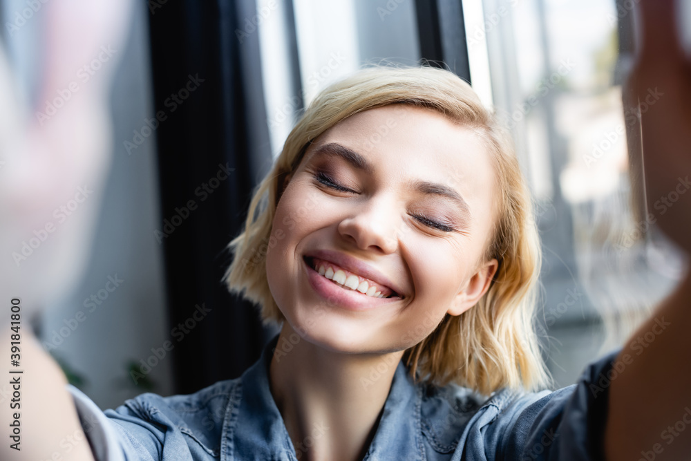 Fototapeta blonde woman smiling with closed eyes
