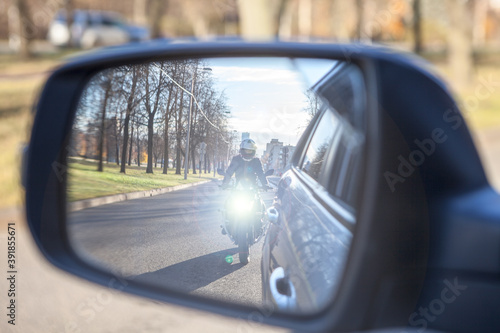 Dazzle lighting from riding motorcycle in side view mirror of car. Dazzling effect concept