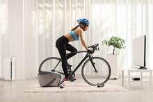Young Woman Cycling With Stationary Bicycle Trainer At Home
