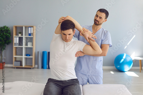 Canvas Print Chiropractor or physiotherapist examining young man's arm to help him cure healt