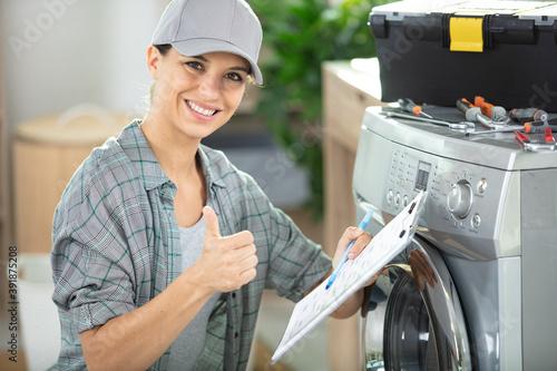 Obraz young woman repairing washing machine - fototapety do salonu