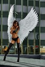 Beautiful Seductive Angel Woman Wearing Lingerie Crouching On The Roof In Big City With Wind In Her Wings Over Cloudy Sky