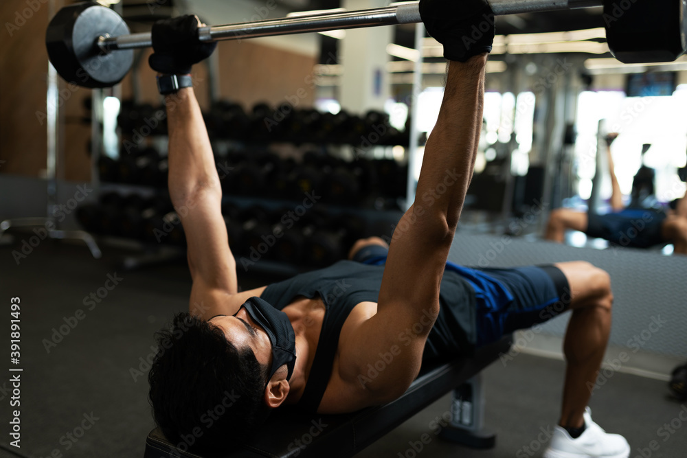 Fototapeta Latin man on a bench lifting weights