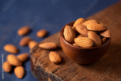 Papel de parede Close-up of raw almonds with a blue background with copy space