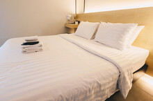View Of Comfortable Bed With Hotel Amenities In Hotel Bedroom Decoration In Cozy Style. Conceptual Of A Room In A Home Where People Sleep.