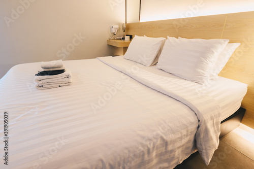Vászonkép View of comfortable bed with hotel amenities in hotel bedroom decoration in cozy style