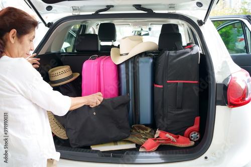 Fotografija La señora está arreglando las maletas y los objetos en la camioneta