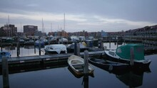 Shot Of The Harbour Of Groningen Where Recreational Boats And Sailships Are Stored, With Flats And Dutch Houses In The Background At Night On A Cold Winter Cloudy Day