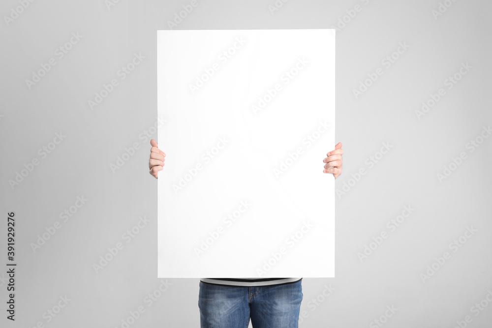 Fototapeta Man holding blank poster on light grey background