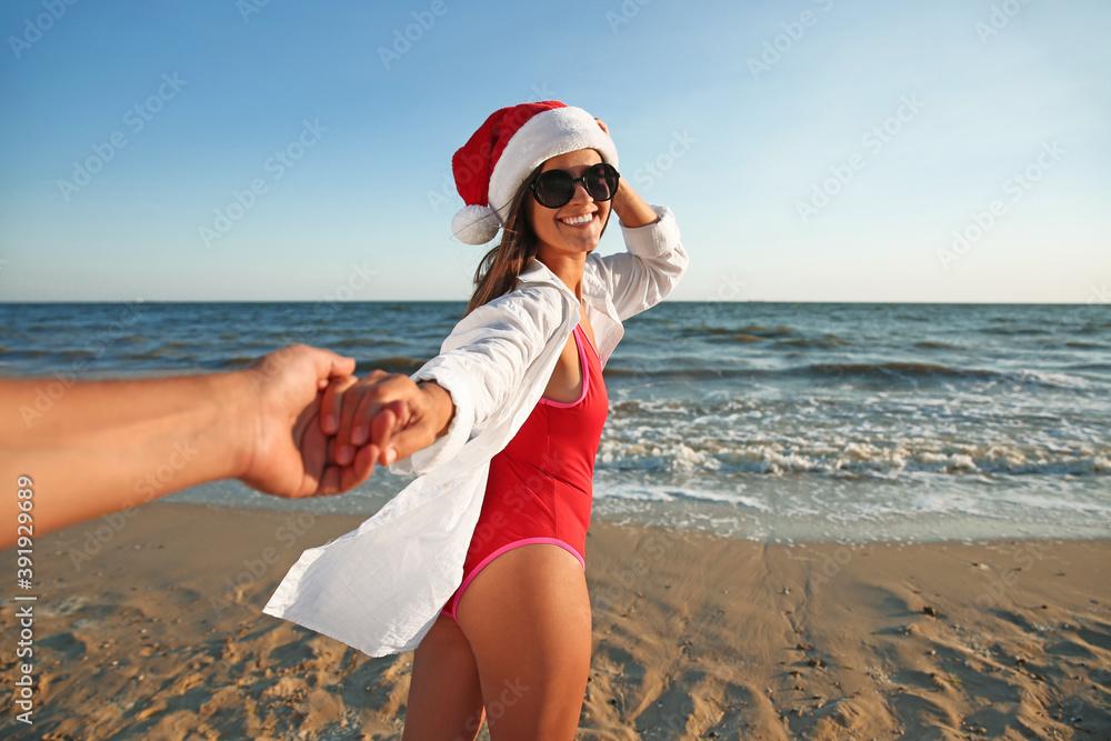 Fototapeta Lovely couple with Santa hat on beach. Christmas vacation