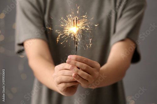 Tela Woman holding burning sparklers against blurred lights, closeup