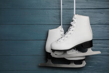 Pair Of White Ice Skates Hanging On Blue Wooden Background. Space For Text