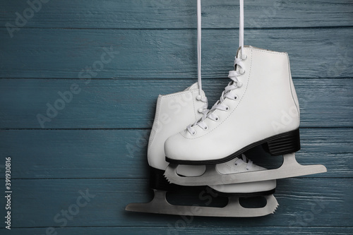Obraz na plátně Pair of white ice skates hanging on blue wooden background