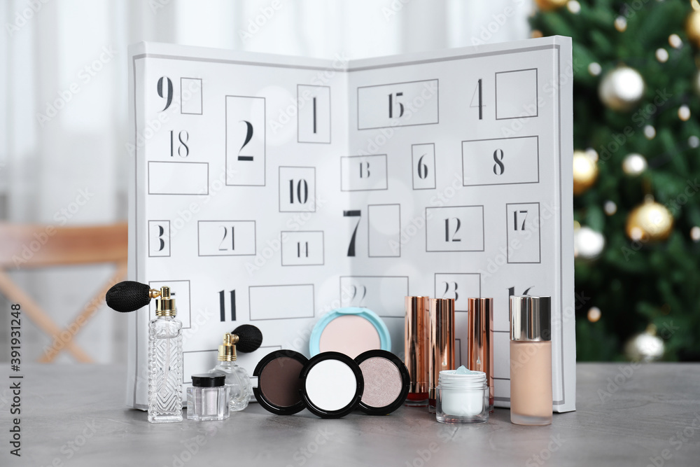 Fototapeta Christmas advent calendar with perfumes, skin care and decorative cosmetics on table
