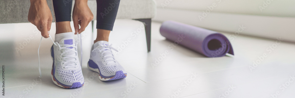 Fototapeta Home workout woman getting ready for training tying her purple running shoes and yoga mat banner panoramic. Fitness during coronavirus, active sport.