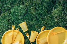 Environmental Pollution. Disposable Plastic Tableware - Plastic Plates, Forks, Spoons, Knives. Yellow Plastic Tableware On Green Grass, Moss Background. Top View. Copy Space. Ban Single Use Plastic