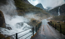 Wooden Bridge Over Wild Waterfall In Norway, Epic Mountain Scenery In The Background, Moody Clouds Of Fog Surrounding The Bridge