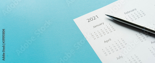Obraz close up top view on white calendar 2021 schedule with pen on blue color background to make appointment meeting or manage timetable each day for design planning work and life concept - fototapety do salonu