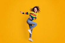 Full Length Photo Of Funny Jumping Woman Dressed Casual Colorful Sweatshirt Dancing Looking Empty Space Isolated Yellow Color Background