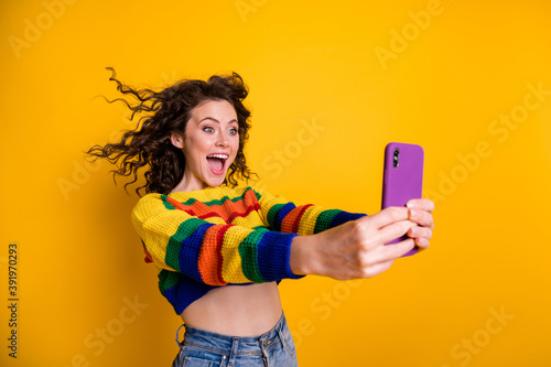 Photo of cheerful cute curly brunette hairdo girl do selfie wear short pullover isolated over shine yellow color background