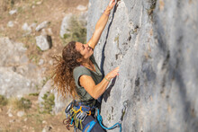 Curly Haired Blonde Young Woman Climbing On Natural Stone