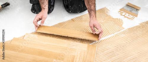 Fototapeta Handwerker verlegt einen atemberaubenden Parkettboden im Fischgräten Muster und setzt gerade ein frisches Brett an  obraz na płótnie