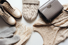Winter Fashion Set Of Woman Clothes In Neutral Tones: Warm Sweater, Hat, Mittens, Shoes And Handbag On White Background. Top View.