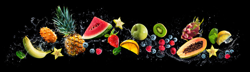 Assortment of fresh fruits and water splashes on panoramic background