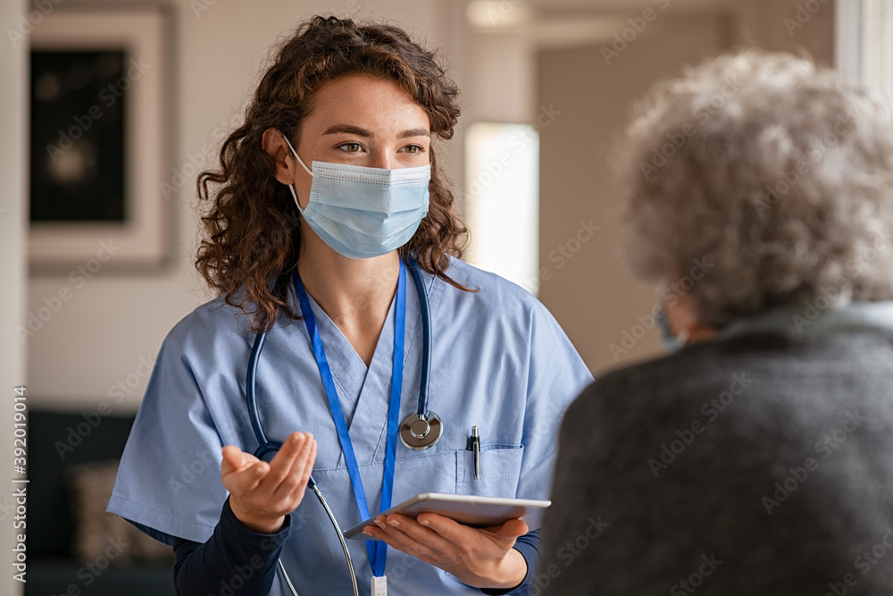 Fototapeta Young doctor visits senior woman with surgical mask