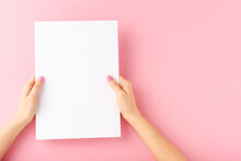 Female Hands Holding Blank White Paper Sheet On Pink Background. Mock Up