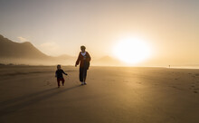 Silhouette Of Young Mother With Her Little Child Walking On Sunshine In Cofete, Fuerteventura, Canary Islands, Spain.