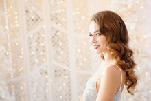 Beautiful Girl On Background Of Bokeh Lights In Silver Dress With Retro Hair Styling, Smiling. Concept Merry Christmas And Happy Holidays