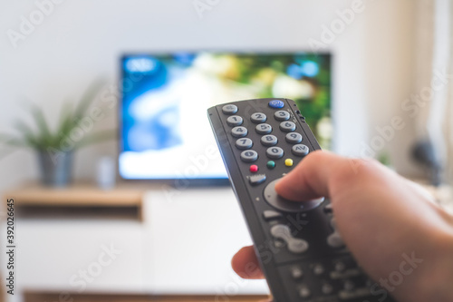 Obraz Male hand is holding TV remote control, streaming on a smart TV. - fototapety do salonu