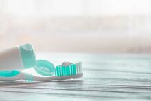 Turquoise Toothbrush With White Toothpaste On The Bristles And A Tube Of Toothpaste On A White Wooden Background