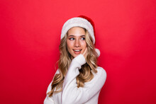 Young Pretty Woman In Warm Clothes In Santa Hat Isolated On Red Background