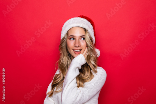 Canvas Print Young pretty woman in warm clothes in santa hat isolated on red background