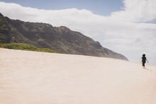 Woman Walks Up Sandy Hill Towards Mountains In Hawaii