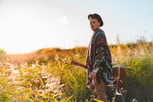Folk Musician With Acoustic Guitar Posing In Poncho In Rural Area