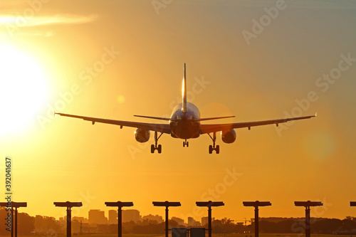 Airplane landing as the sun sets.