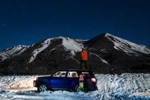 Rear View Of Standing On Off-road Car Against Mountain During Winter At Night