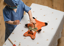Young Child Wearing Medical PPE Administers A Shot To A Plush Toy Fox Hand Puppet